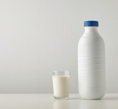 Transparent glass with fresh organic milk near plastic riffled blank bottle with blue cap isolated on side of white table Space for your text above Retail set, rich texture